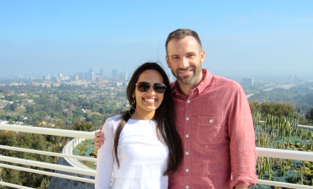 Ryan and Sonia pose at The Getty Center, with a view of downtown Los Angeles behind them.